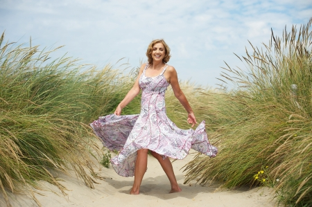 Portrait of a beautiful middle aged woman dancing in the sand at the beach photo