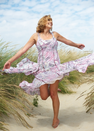 Portrait of a carefree middle aged woman dancing outdoors