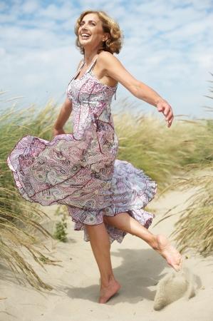 Zorgeloos portret van een mooie vrouw van middelbare leeftijd dansen in openlucht