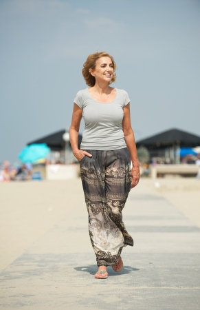 Portrait of a beautiful older woman walking at the beach photo