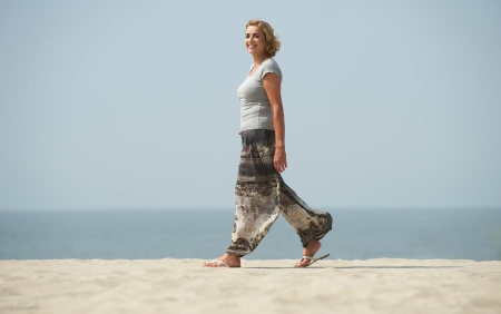Profile portrait of a mature woman walking at the beach photo