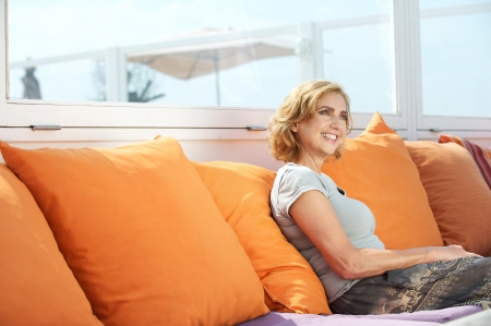 Closeup portrait of an attractive middle aged woman sitting on sofa outdoors photo