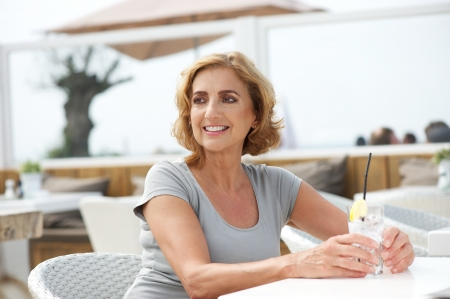 Horizontal portrait of a happy woman relaxing with a drink of water at outdoors restaurant photo