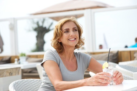 Closeup portrait of an older woman relaxing outdoors with a glass of water photo