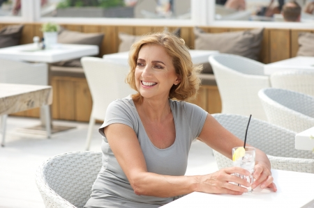 Portrait of a woman sitting outdoors with a glass of water photo
