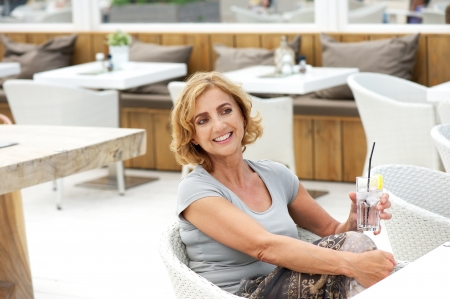 Closeup portrait of a beautiful woman relaxing at restaurant with glass of water photo