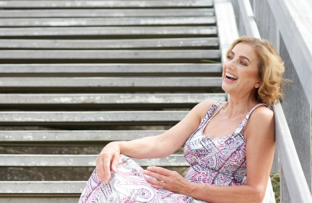 woman stairs: Portrait of a beautiful older woman sitting on stairs and laughing outdoors