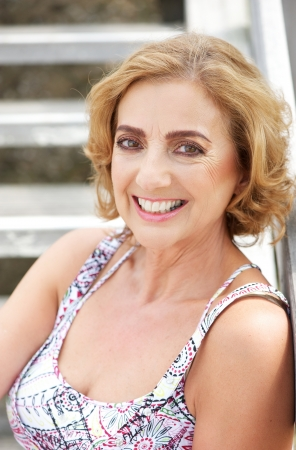 Closeup portrait of an attractive middle aged woman smiling outdoors photo
