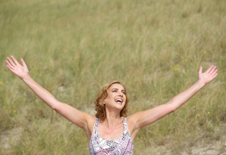 spreading arms: Portrait of a carefree woman standing with arms outstretched  Stock Photo