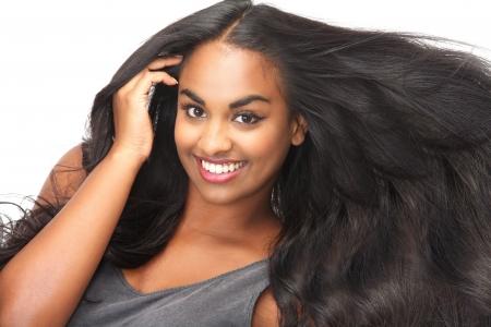 Portrait d'une belle femme souriante avec les cheveux débordants isolé sur blanc