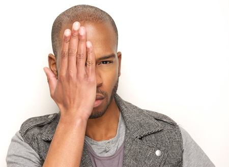 hand covering eye: Closeup portrait of a male fashion model with hand covering half face