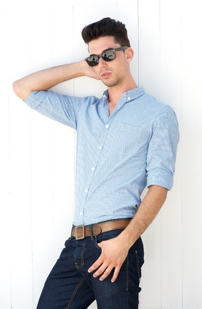 Portrait of a handsome male fashion model posing with sunglasses photo