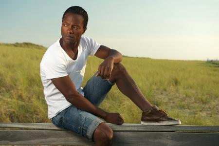 modelos negras: Retrato de un hombre joven y guapo sentado solo fuera