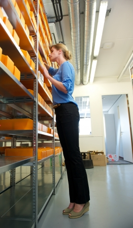 Portrait of a female employee searching through boxes on shelves photo