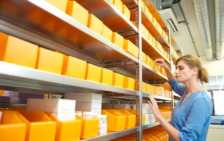 Horizontal portrait of a female worker organizing boxes on shelves photo