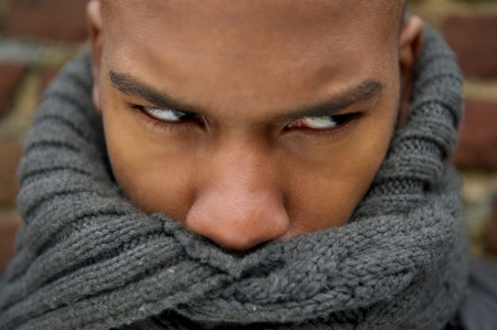 Closeup portrait of a handsome man with scarf covering face photo