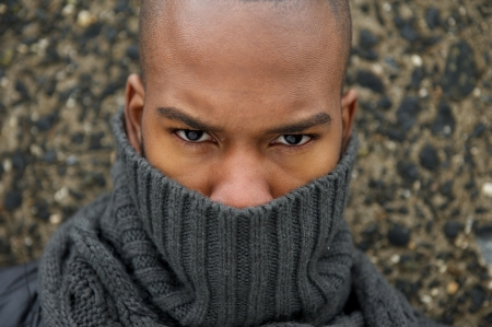 Closeup portrait of male fashion model with gray winter scarf covering face photo