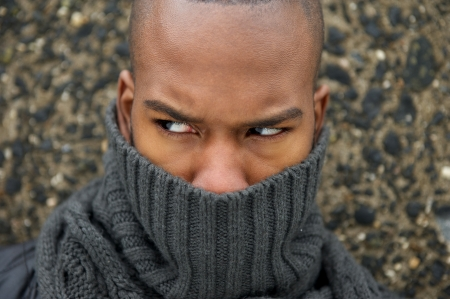Closeup portrait of a black male fashion model with gray scarf covering face photo