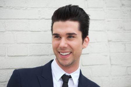 hair tie: Portrait of a cheerful young man in business suit smiling outdoors
