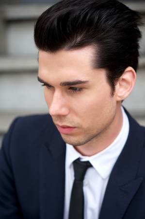 Closeup profile portrait of a handsome young man in suit and tie photo