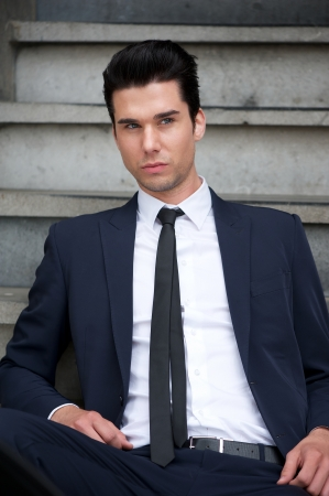 Portrait of an attractive male fashion model sitting on stairs photo