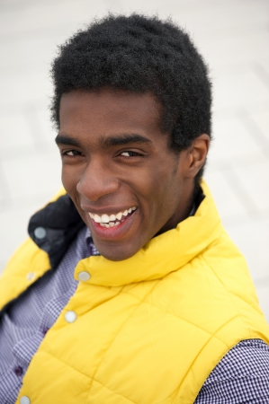 Closeup portrait of a happy young man smiling outside photo