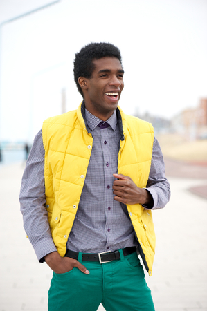 Portrait of a cheerful young man in colorful clothing standing outdoors photo
