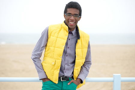 Portrait of a happy young man with glasses and wearing colorful clothing photo