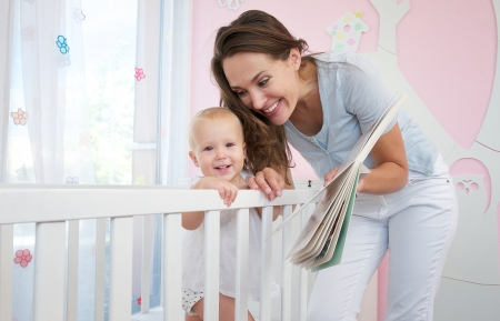 Portrait of a happy mother with smiling baby together in bedroom  photo