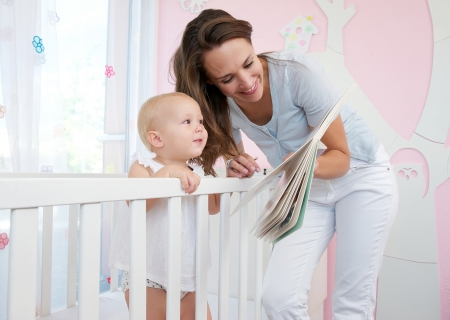 Portrait of mother and baby reading together from a book in bedroom Stock Photo - 22308032