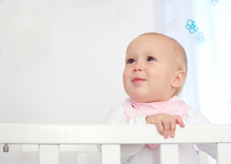 copy sapce: Closeup portrait of an adorable baby standing in crib