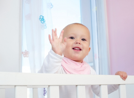 Closeup portrait of a cute baby waving hello with hand photo