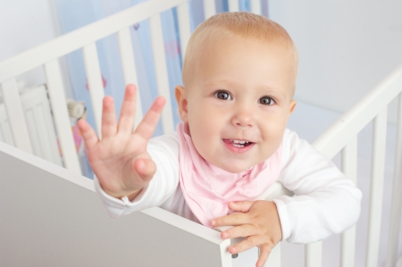 baby crib: Closeup portrait of a cute baby waving hello and smiling from crib Stock Photo