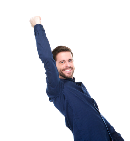 Portrait of a successful young man smiling with arms raised on isolated white background photo