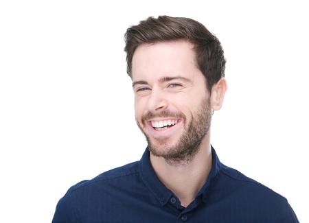 Close-up portret van een vrolijke jonge man glimlachend op witte achtergrond Stockfoto