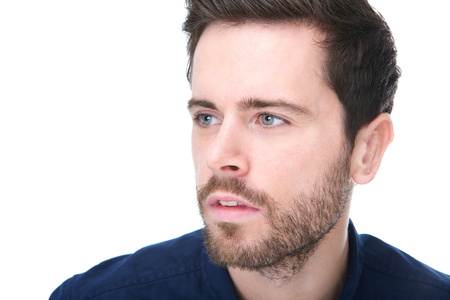 Closeup portrait of an attractive young man with beard and serious expression on face