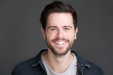 Close-up portret van een lachende jonge man op zoek naar camera