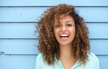 Portret van een vrolijke jonge Afrikaanse vrouw lachend