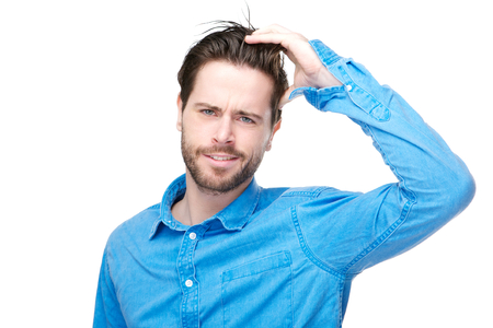 confused man: Portrait of a confused male individual with hand in hair Stock Photo
