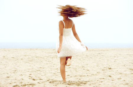 Portrait of a young woman dancing on the sand at the beach photo