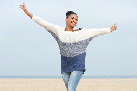 Closeup portrait of a beautiful young woman with cheerful expression and arms outstretched walking at the beach Stock Photo