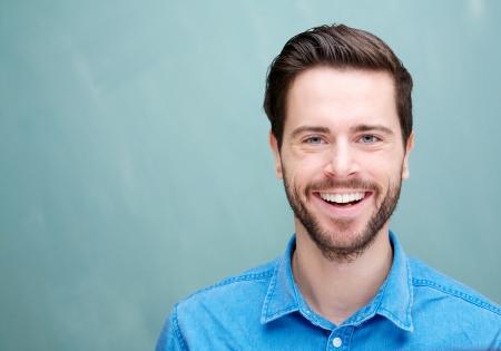 ひげを笑顔でハンサムな若い男のクローズ アップの肖像画