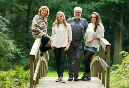 Portrait of a happy family with mother father and daughters standing on bridge in the forest photo