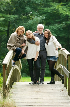 Portrait of a happy family standing together on a bridge in the forest photo