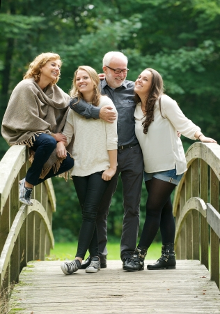 Portrait of a beautiful happy family standing together in a bridge in the woods photo