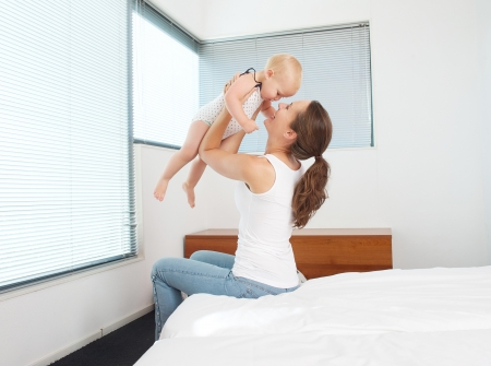 mother holding baby: Portrait of a happy mother playing with baby in bedroom