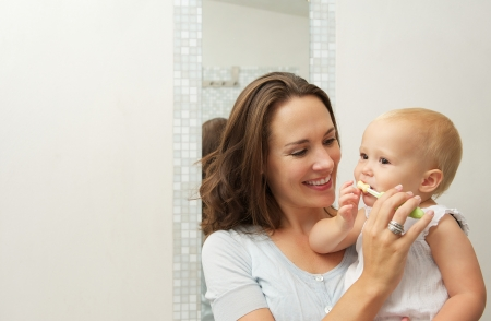 Horizontal portrait of a smiling mother teaching cute baby how to brush teeth with toothbrush photo