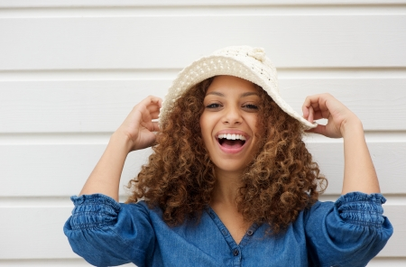 Closeup portrait of a cheerful young woman with hat laughing outdoors photo