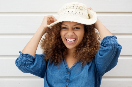 mixed race person: Portrait of a cheerful carefree woman laughing and wearing summer hat