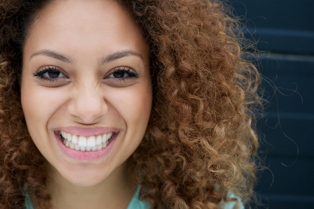 Closeup portrait of a young woman smiling with happy expression on face photo